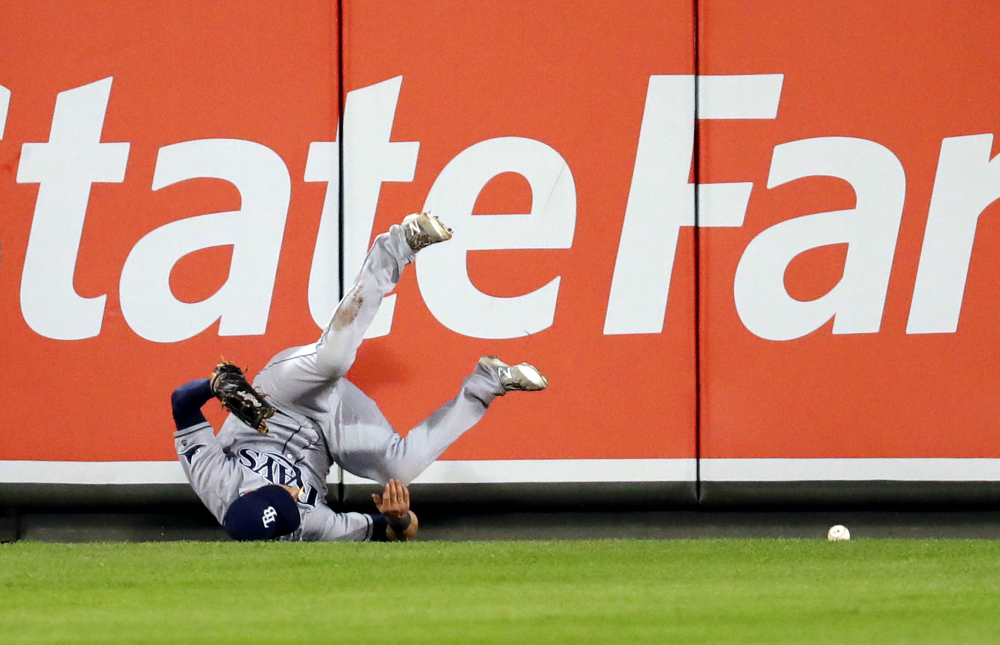 Rays center fielder Kevin Kiermaier collides with the outfield wall as he is unable to field a two-run double by J.J. Hardy of the Orioles during the first inning of Thursday's game in Baltimore. Tampa Bay pulled out a 7-6 victory.