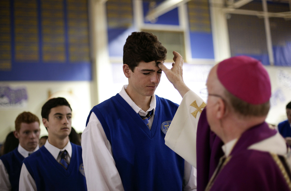 Students line up on Ash Wednesday in 2014 at Santa Margarita Catholic High School in Rancho Santa Margarita, Calif. A new study published this week by a father-daughter researcher team says religion is bigger than Facebook, Google and Apple combined.