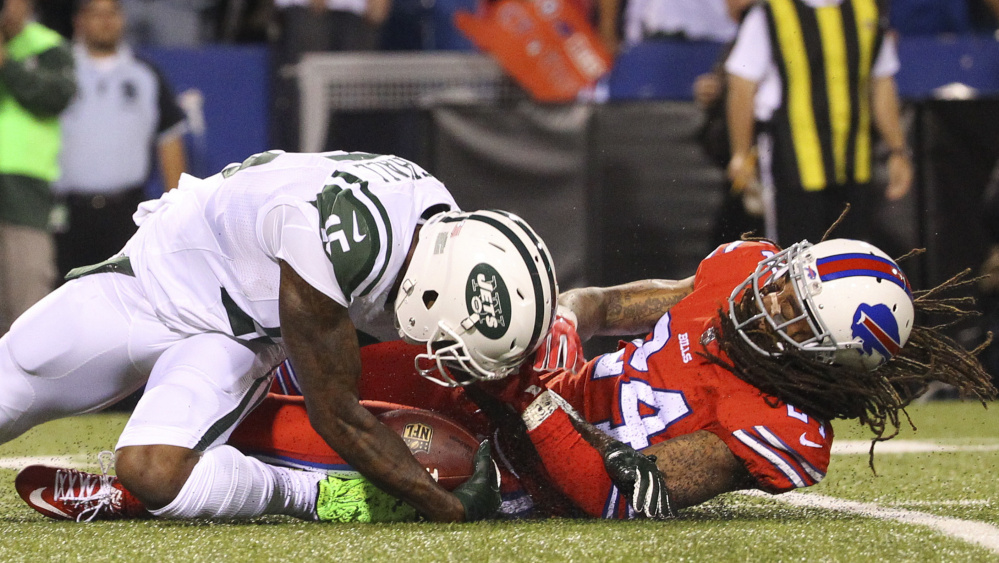 Brandon Marshall of the New York Jets, left, hurt his left knee Thursday night while being tackled by Stephon Gilmore of Buffalo, and thought he was headed to the injury list. Yet 10 minutes later he was back in the huddle.