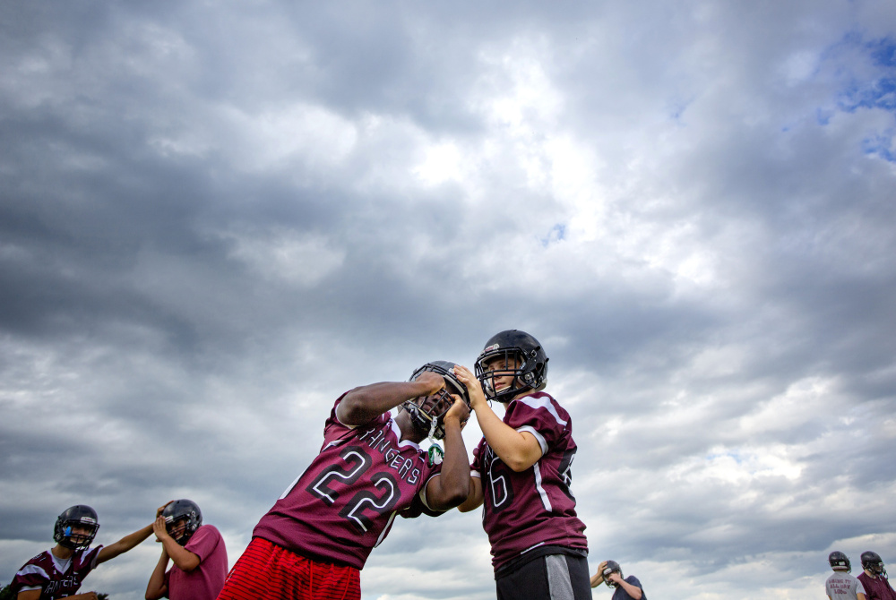 Greely High School freshmen Mike Flaherty, right, and Naveen Caron go through stretching exercises during a recent practice in Cumberland. With participation down – only five freshmen entered the football program this year – the school decided to drop its junior varsity team.