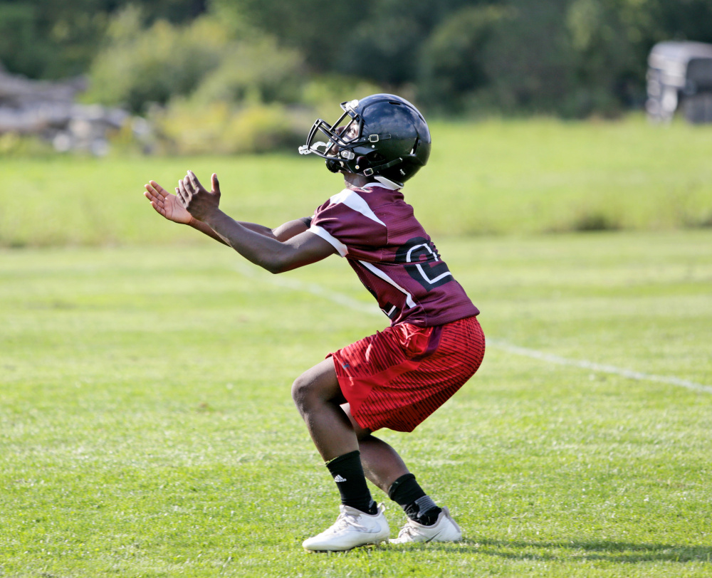 Freshman Naveen Caron gets set to receive a kick during a special-teams drill at Greely High School football practice. Greely joined South Portland and Massabesic in eliminating junior varsity teams this year; Windham and Cheverus dropped their freshman football schedules.