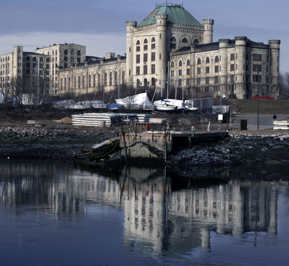 The former Navy prison at the Portsmouth Naval Shipyard in Kittery is reflected in the Piscataqua River.