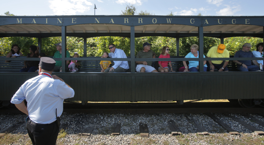 Volunteer conductor Brian Tutlis waits for passengers to reboard the train after a stop along Portland's waterfront. A plan for Gray to put nearly $500,000 into a project to move the operation to the town has proponents and detractors.