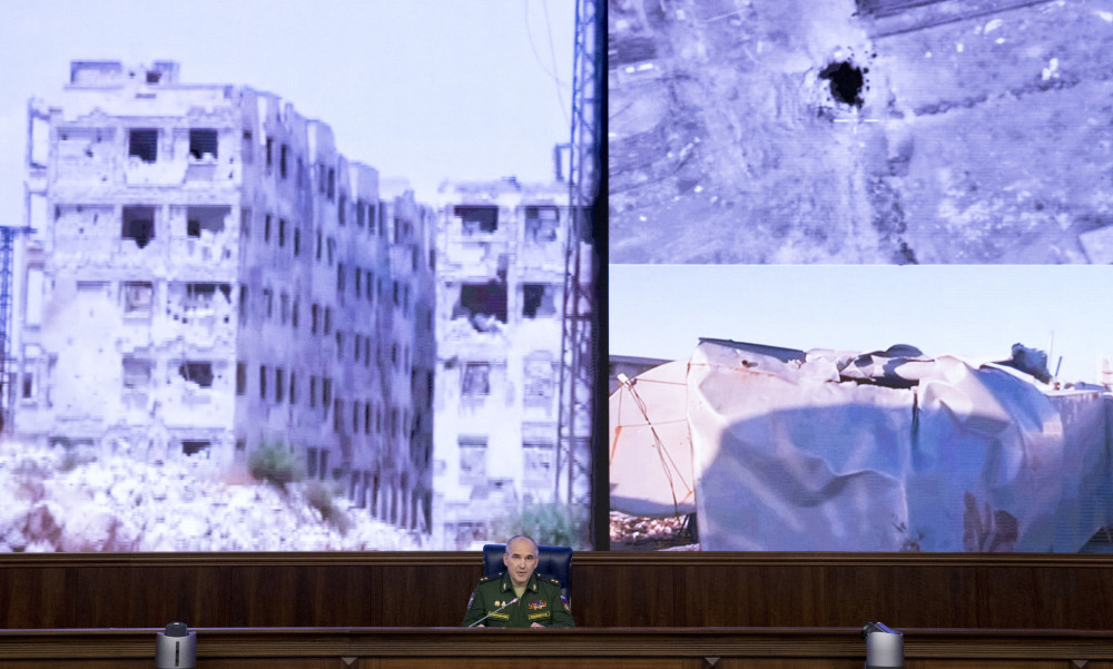 Lt. Gen. Sergei Rudskoi of the Russian military's General Staff speaks to the media in Moscow on Monday about the failure of the cease-fire in Syria, with images of the conflict behind him. He blamed rebel violations for ending the truce.