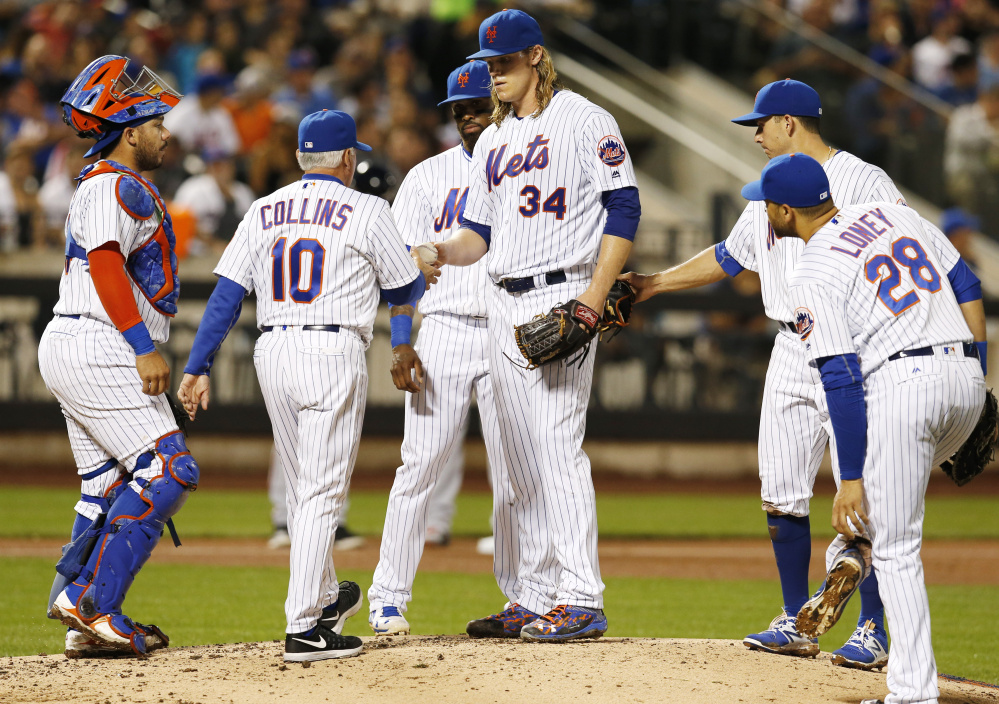 Manager Terry Collins takes the ball from Mets starting pitcher Noah Syndergaard, center, during the fourth inning of a 7-3 loss at home to Atlanta on Monday night. Syndergaard fell to 13-9 in losing to the Braves, who have the worst record in the NL.