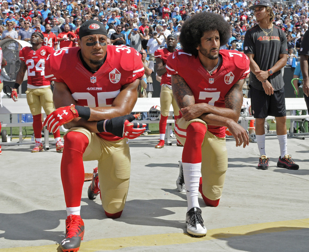 San Francisco's Colin Kaepernick, right, was joined by teammate Eric Reid in taking a knee during the national anthem before their game against Carolina last Sunday.