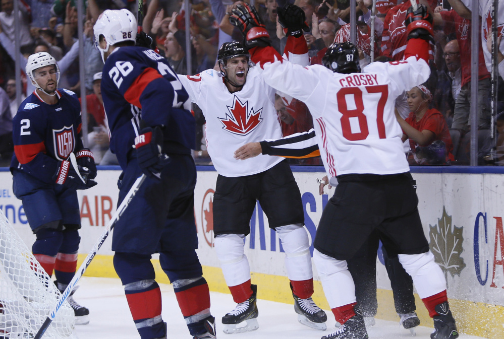 Sidney Crosby, 87, celebrates a Team Canada goal with John Tavares as Team USA defensemen Blake Wheeler, foreground, and Matt Niskanen can only skate away Tuesday night. The U.S. won't advance out of group play after a 4-2 loss.