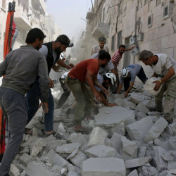 Rescue workers search through rubble after airstrikes in Aleppo, Syria, on Wednesday. A volunteer aid group said 24 were killed in a series of bombings in the besieged city.