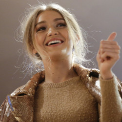 Model Gigi Hadid, hosted by Max Mara, salutes fans from the flagship store during a fashion event in Milan, Italy, Wednesday.