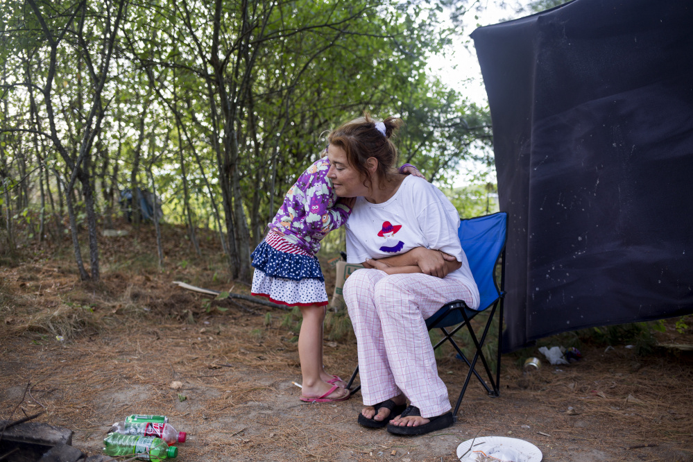 Arianna hugs Chrissy for warmth on a chilly morning at the Portland campsite known as Tent City.
