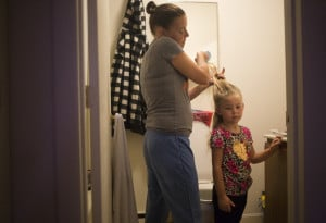 Chrissy brushes Arianna's hair in preparation for her first day of kindergarten. School had started the week before, when they were in the process of moving to Auburn.
