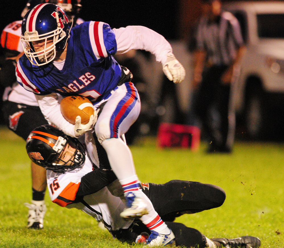Messalonskee running back Austin Pelletier is tackled by Brunswick defender Aaron Gary during Friday night's game in Oakland. It was tough going for Messalonskee's ball carriers as the Eagles were shut out, 42-0.