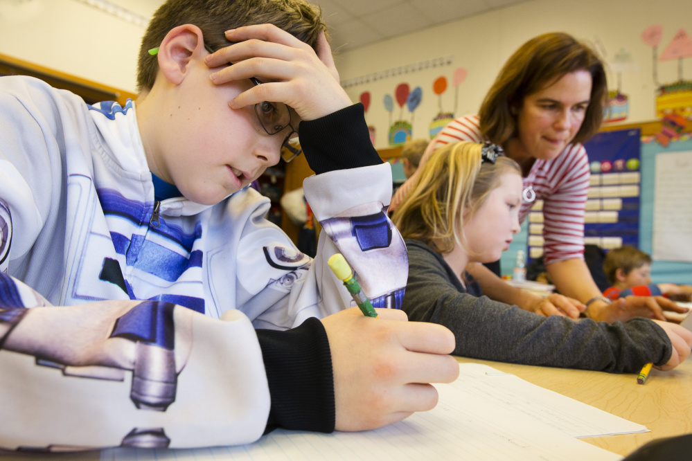 In a Jan. 27 photo, Chebeague Island School fifth-grader Logan Beaupré works on a writing project while his teacher, Kristin Westra, helps third-grader Sadie Todd in the Grades 3-5 classroom. Nationwide, there were 60,000 fewer teachers than needed in 2015, and the deficit could reach 100,000 by 2018.