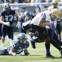 DeAndre Scott, left and Darius Greene, center, of Maine try and take down John Miller of James Madison in the first half on Saturday in Orono. James Madison rallied in the fourth quarter for a 31-20 win.