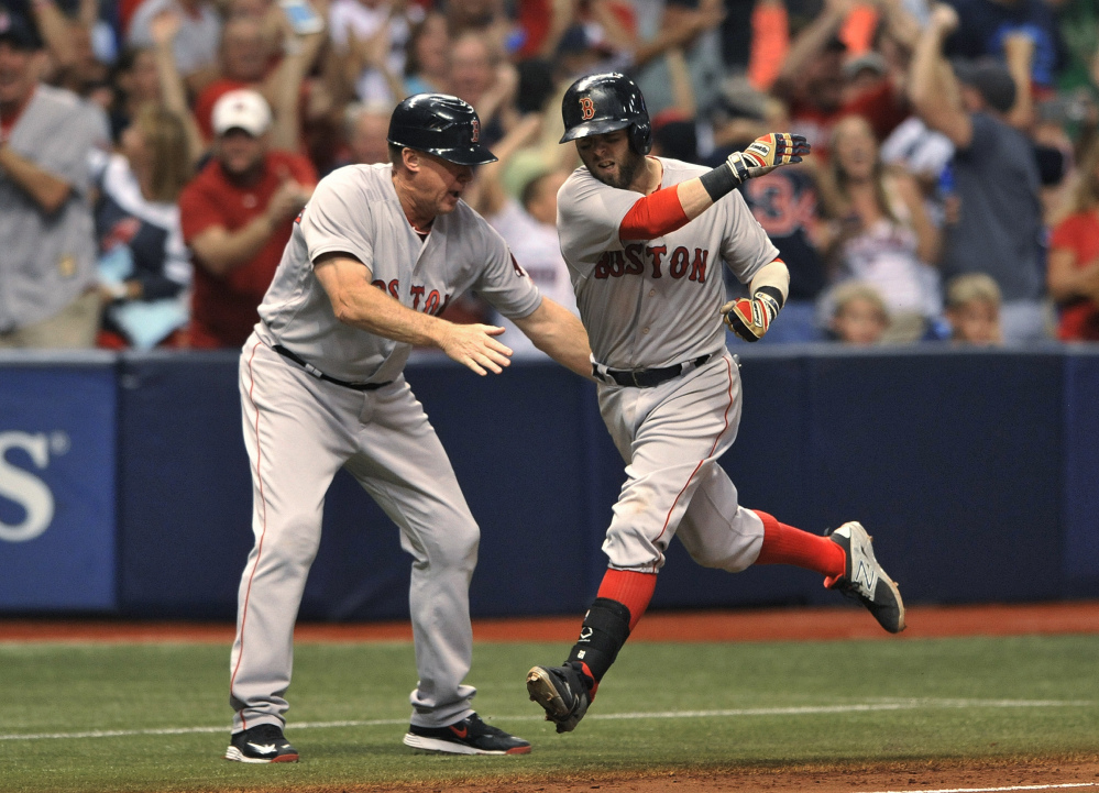Boston third base coach Brian Butterfield, left, congratulates Dustin Pedroia, who circles the bases after hitting a grand slam off Tampa Bay reliever Danny Farquhar in the seventh inning oon Saturday in St. Petersburg, Fla. The Red Sox went on to a 6-4 win,