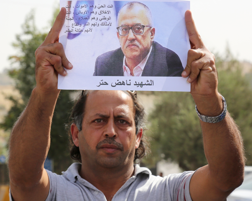 A man holds a picture of Jordanian writer Nahed Hattar, who was shot dead Sunday in front of the courthouse where he was on trial.