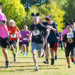 Participants, many wearing pink clothing and mouse ears, sprint off from the starting line at the Miles Across Maine for Breast Cancer Awareness fundraiser Saturday in Augusta.