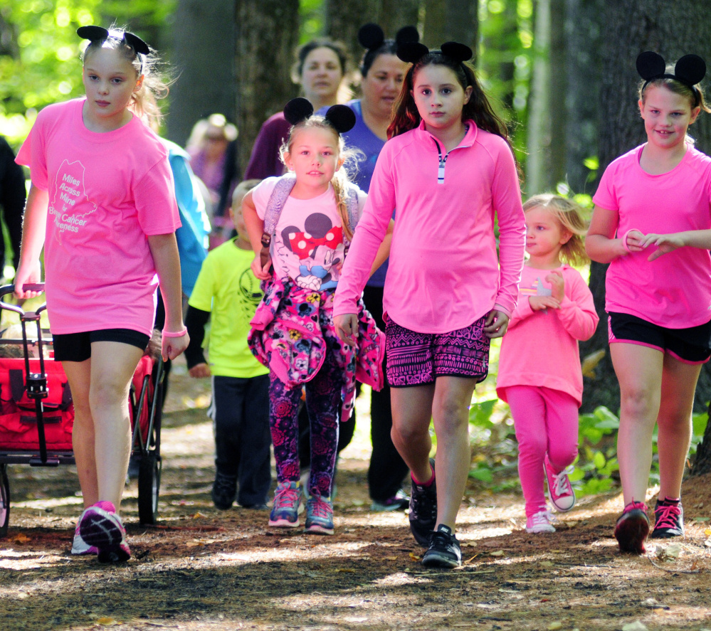 Children walk through the woods during the Miles Across Maine for Breast Cancer Awareness event Saturday in Augusta. Some wore Mickey Mouse ears in memory of the event organizer's grandmother, who loved to take Disney vacations.