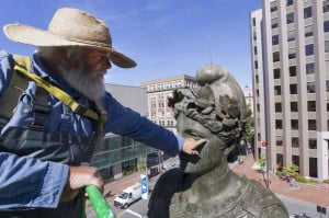 "Jonathan Taggart, who owns Taggart Objects Conservation of Georgetown, points out the corrosion on the face of the ""Our Lady of Victories"" statue in Monument Square on Monday. Taggart was contracted by the city to put a new coat of protective coating on the statue."