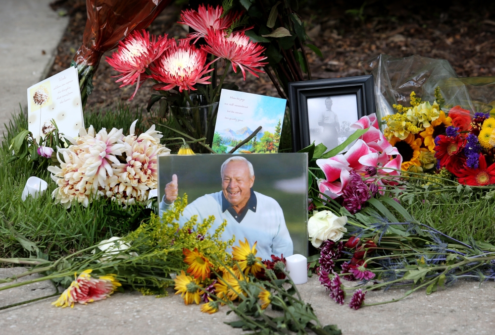 Flowers and mementos adorn a makeshift memorial honoring the late golf great Arnold Palmer on Monday at Palmer's parking spot at the Golf Channel studios in Orlando, Fla.