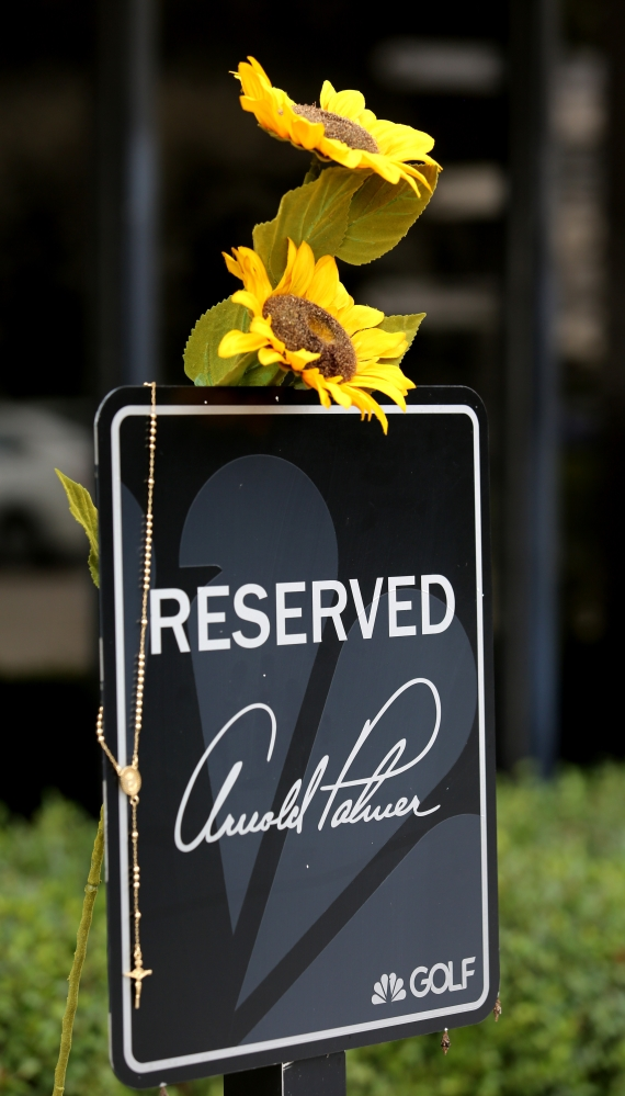 Flowers and rosary beads hang from a sign at Palmer's parking spot at the Golf Channel. Palmer was beloved for his kind nature as much as his golf game.