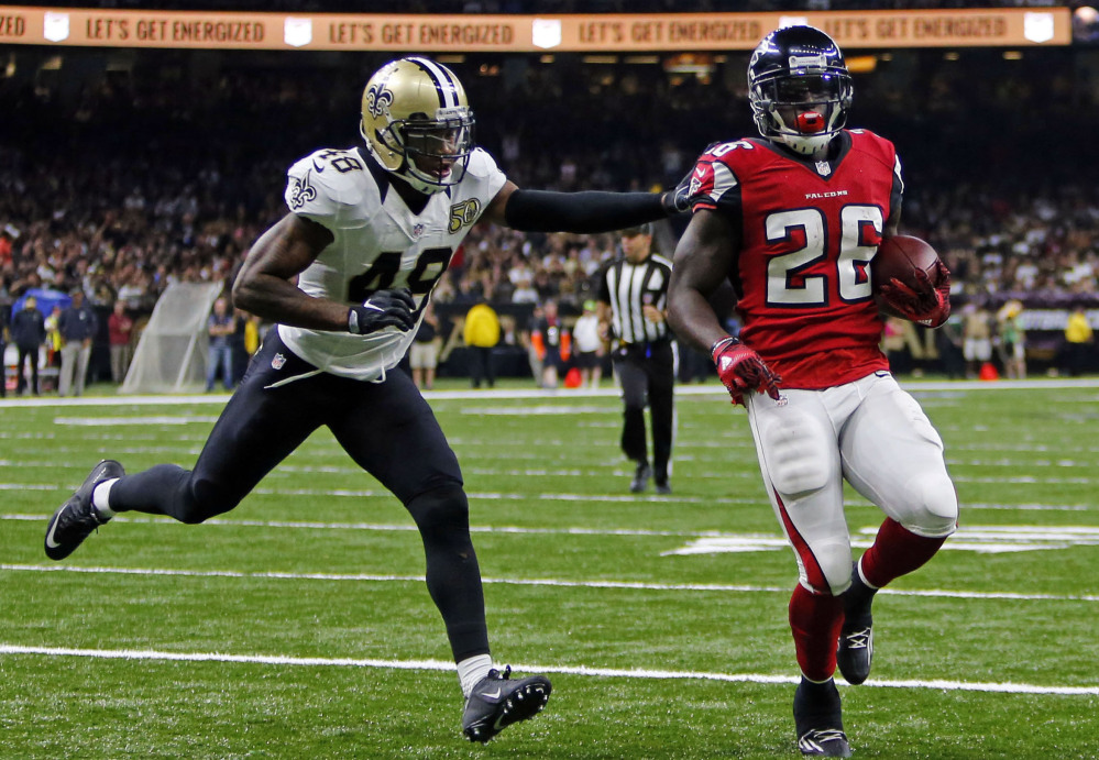 Falcons running back Tevin Coleman scores on a 6-yard touchdown run as the Saints' Vonn Bell gives chase in the third quarter of Atlanta's 45-32 win Monday in New Orleans. Coleman rushed for three touchdowns.