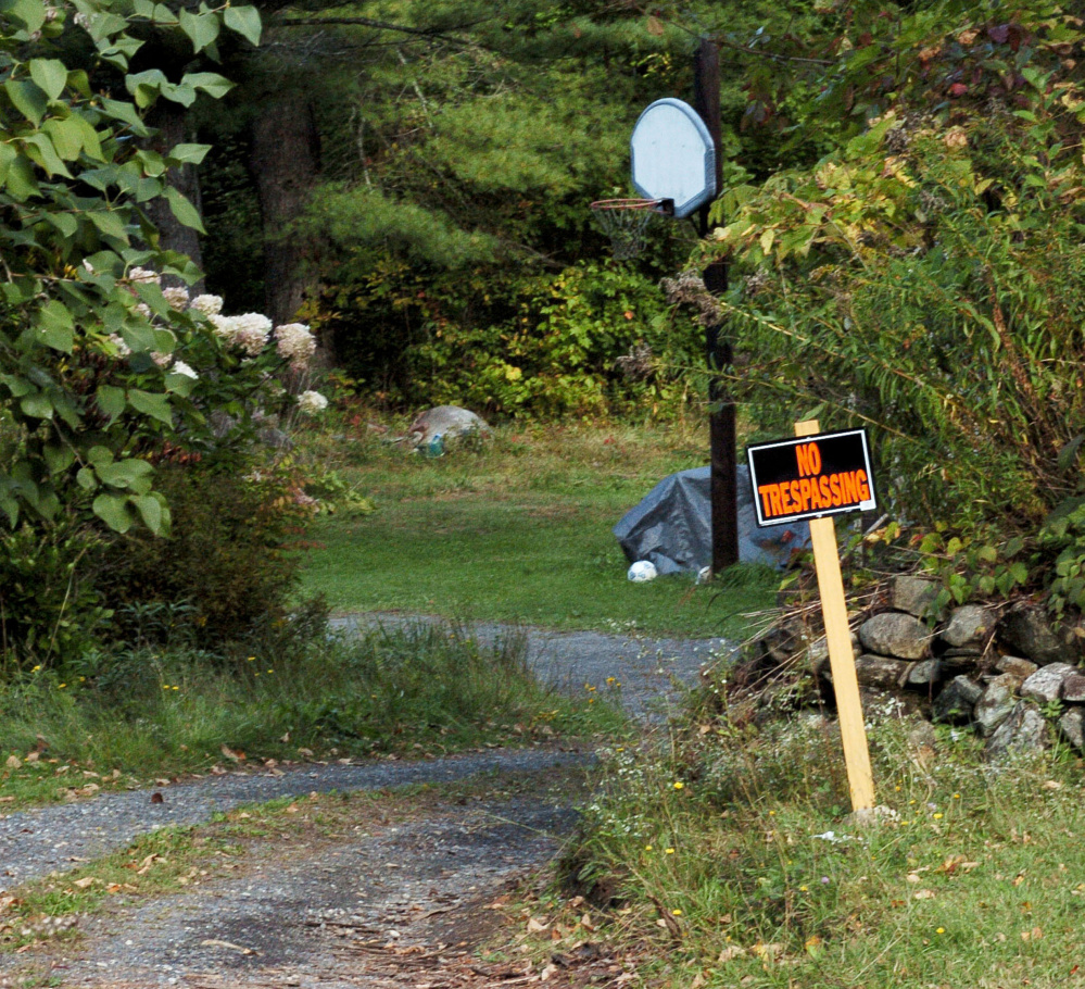 """A """"No Trespassing"""" sign is posted Tuesday in the driveway at the home of Alan and Laurelle Tieman on Norridgewock Road in Fairfield. Police found the body of their daughter-in-law, Valerie Tieman, partially buried on the property last week. The woman's husband, Luc Tieman, is charged with murder in connection with the killing."""