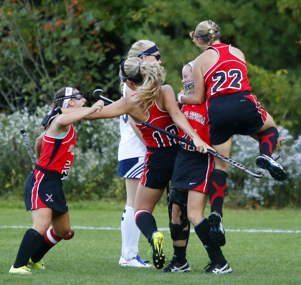 Scarborough teammates Lily Nygren, left, Victoria Timm, second from left, Ashley Levesque, center, and Kristen Levesque celebrate after beating Westbrook 2-1 in double overtime on Monday in Westbrook.