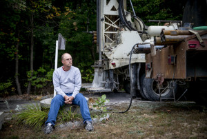 """With a new well being drilled on his property in Standish, Bob Boynton sits atop the concrete casing of his shallow dug well, which ran dry a week ago as southern Maine and much of New England endure the region's worst drought in more than a decade. """"It really caught me off guard,"""" Boynton said."""