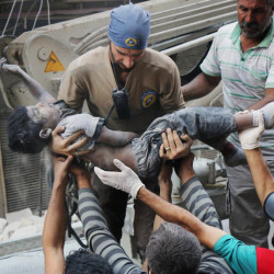A civil defense worker carries the body of a child after airstrikes hit Aleppo, Syria, on Tuesday. Save the Children says 30 to 40 percent of those trapped in Aleppo are children.