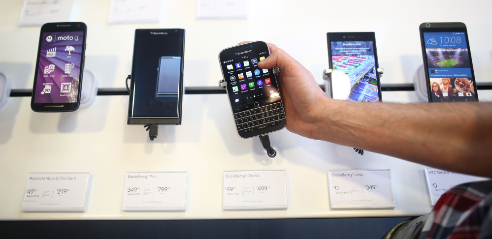 An employee holds a BlackBerry Classic smartphone at a store in Waterloo, Ontario. BlackBerry is handing over production of the phones to overseas partners.