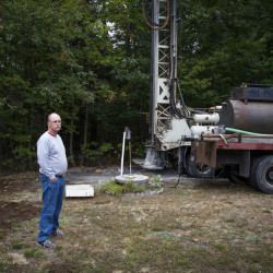 Bob Boynton of Standish stands next to his hand dug well on Sept. 23. Boynton hasn't run out of water in 25 years, but his well ran dry recently. Now, he has to drill a new well and is borrowing water from his neighbor via a garden hose.