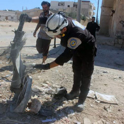 Members of Syrian Civil Defense inspect cluster bombs in the Khan Sheikhoun neighborhood of Idlib, Syria, on Thursday.