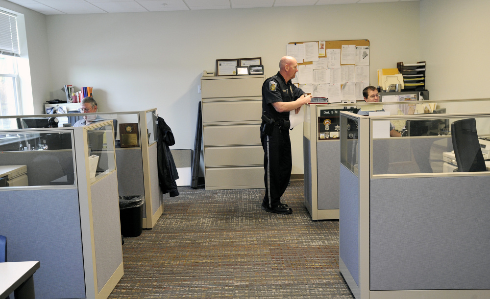 """Officers and detectives work in the new Gorham public safety building Gorham on Tuesday. Police share the renovated complex with the fire department, where Chief Robert Lefebvre says, """"Now we feel like a professional organization."""""""