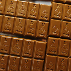 In this Monday, Sept. 19, 2016, photograph, candy bars marked with Colorado's new required diamond-shaped stamp noting that the product contains marijuana are shown in the kitchen of BlueKudu candy in the historic Five Points District of Denver. State officials require the stamp to be put directly on edibles after complaints that the treats look too much like their non-intoxicating counterparts.
