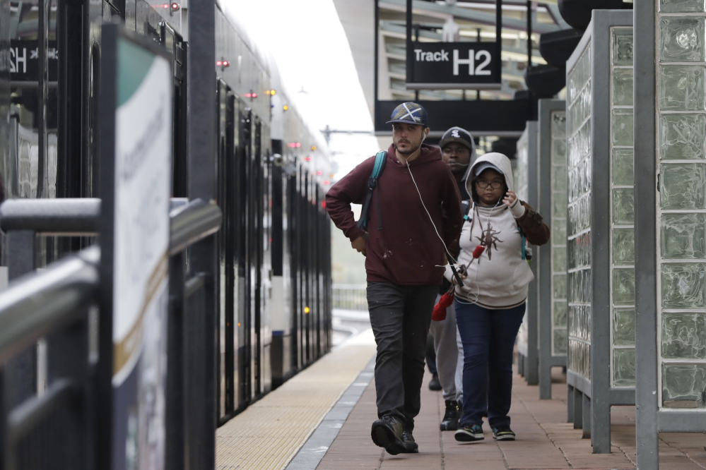 Commuters walk near a light rail train at the Hoboken Terminal Friday in New Jersey. Commuters are using alternative travel in and out of Hoboken a day after a commuter train crashed into the rail station, killing one person and injuring more than 100 people.