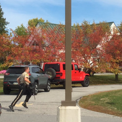 A Kennebec County sheriff's deputy runs across the driveway of the Camden National Bank branch in Manchester on Friday in response to a report of a robbery.
