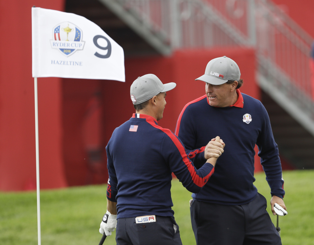United States' Phil Mickelson celebrates with teammate Rickie Fowler after Fowler chipped in on the ninth to win the hole during a foresomes match at the Ryder Cup golf tournament Friday at Hazeltine National Golf Club in Chaska, Minn.