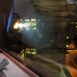 "Olivia Stephenson of Lincoln, R.I., covers the lens of a flashlight as she messages back two light pulses, meaning ""thank you,"" to people in surrounding buildings from her hospital room in Providence, R.I. Businesses around the Hasbro Children's Hospital flash their lights on and off every night as a way to say goodnight to sick children inside. At right, skyline lights illuminate downtown as seen from the hospital."