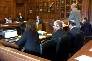 Flanked by his attorneys, Gregory Nisbet, second from left, who is charged with six counts of manslaughter in connection with a 2014 fire at a Portland apartment building that he owned, listens to Assistant Attorney General John Alsop question Daniel Young, an investigator for the Office of the Maine State Fire Marshal, in Cumberland County Superior Court on Friday.