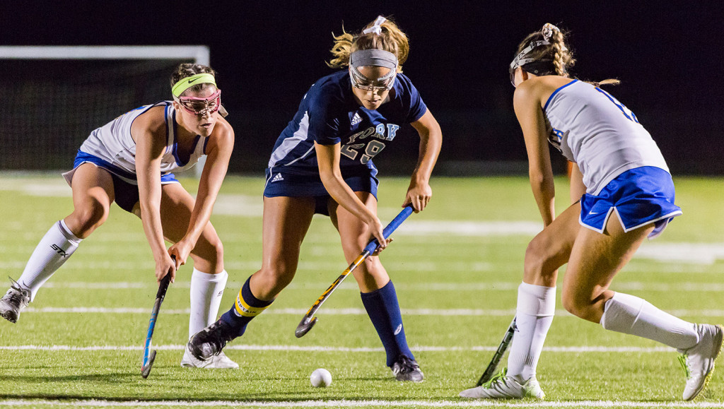 York senior Lily Posternak duels with Falmouth's Sydney Bell, left, and Brienn Douglas during Monday night's game at Falmouth. York stayed unbeaten with a 5-0 win.