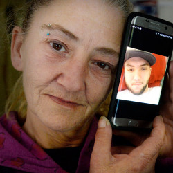 Cheryl Methot, the mother of Jonathon Methot, who was shot early Monday morning in Biddeford, holds a phone with a photo of her son Friday. Shawn Patrick Ouellette/Staff Photographer