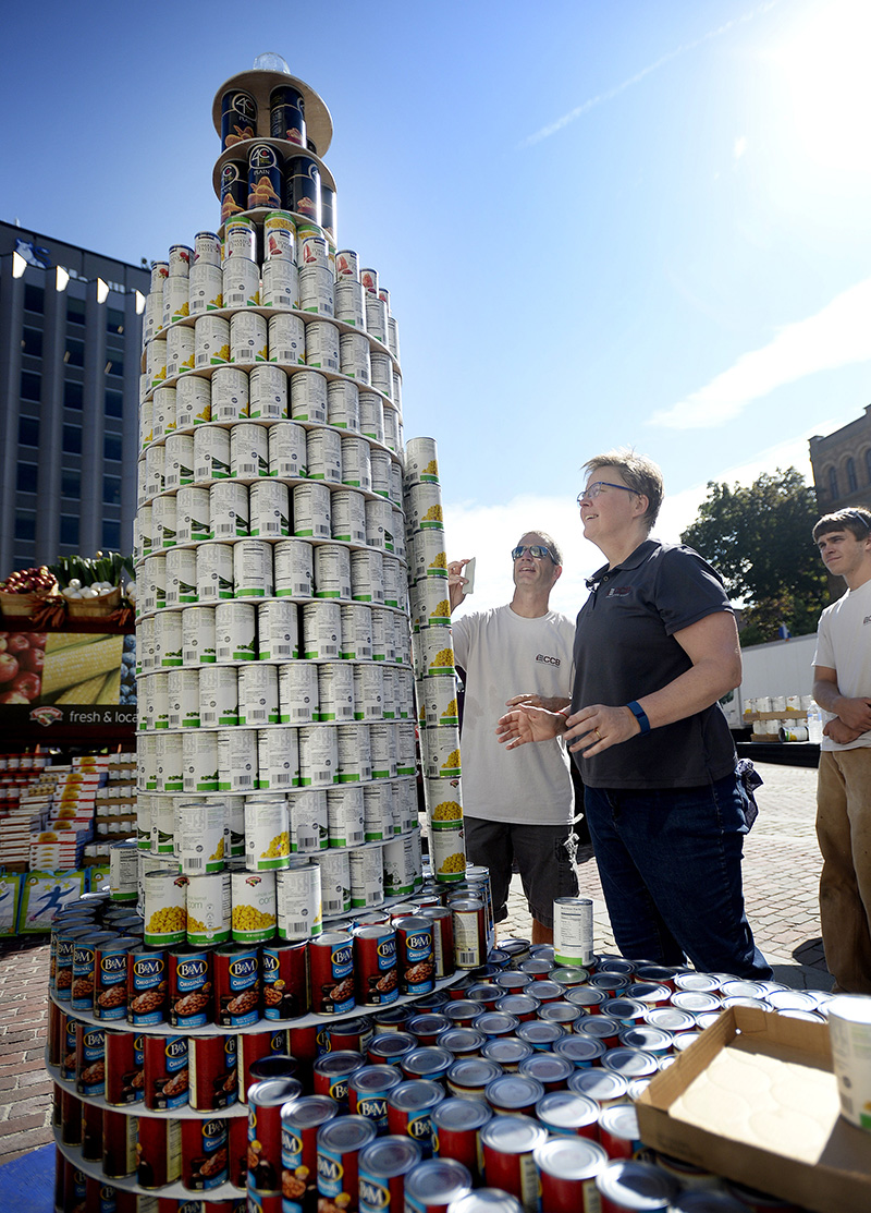 Hundreds of people and local organizations kicked off United Way of Greater Portland's annual campaign with a food drive and sculpture contest in Monument Square on Friday. Sean Ferguson, left and Beth Sturtevant of CCB Inc. work together to build a replica of Bug Light out of donated cans