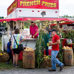 John Frake, who works for Steve's French Fries, enjoys traveling to different fairs and meeting new people. Here he works at the Oxford County Fair in Oxford.