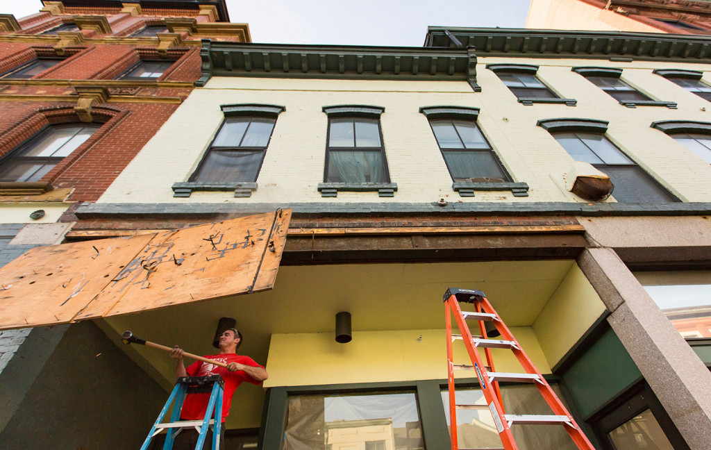 Josh Duball, a worker for Class Acts Property Management, demolishes the last remnant of the Paul's Food Center sign at 585 Congress St. on Tuesday. Portland Flea-for-All plans to open at the location Oct. 6. Ben McCanna/Staff Photographer