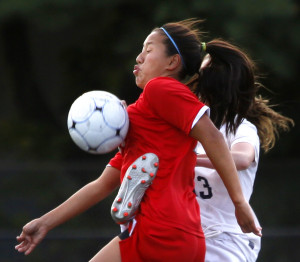 Sophie Chase of South Portland runs through a clear attempt by Cecilia Ritter of Portland in Wednesday's girls' soccer game at Portland. Derek Davis/Staff Photographer