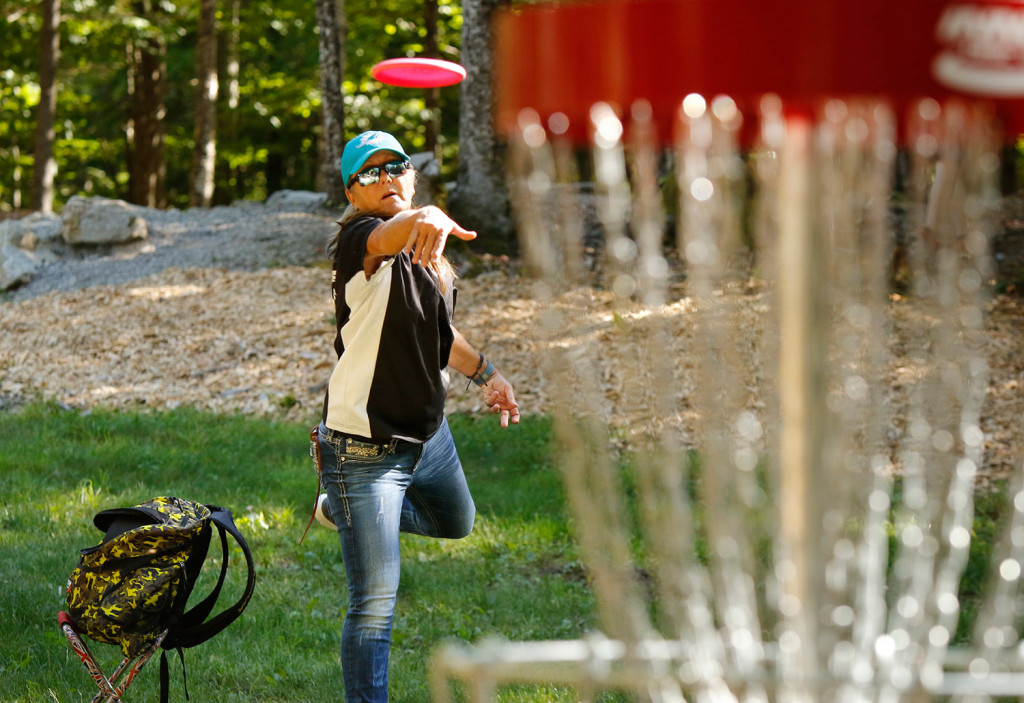 Sandy Gast of Florida releases a disc toward a basket Wednesday while practicing at the Sabattus Disc Golf Complex. Gast is a two-time world champion in the senior grand master category. Gregory Rec/Staff Photographer