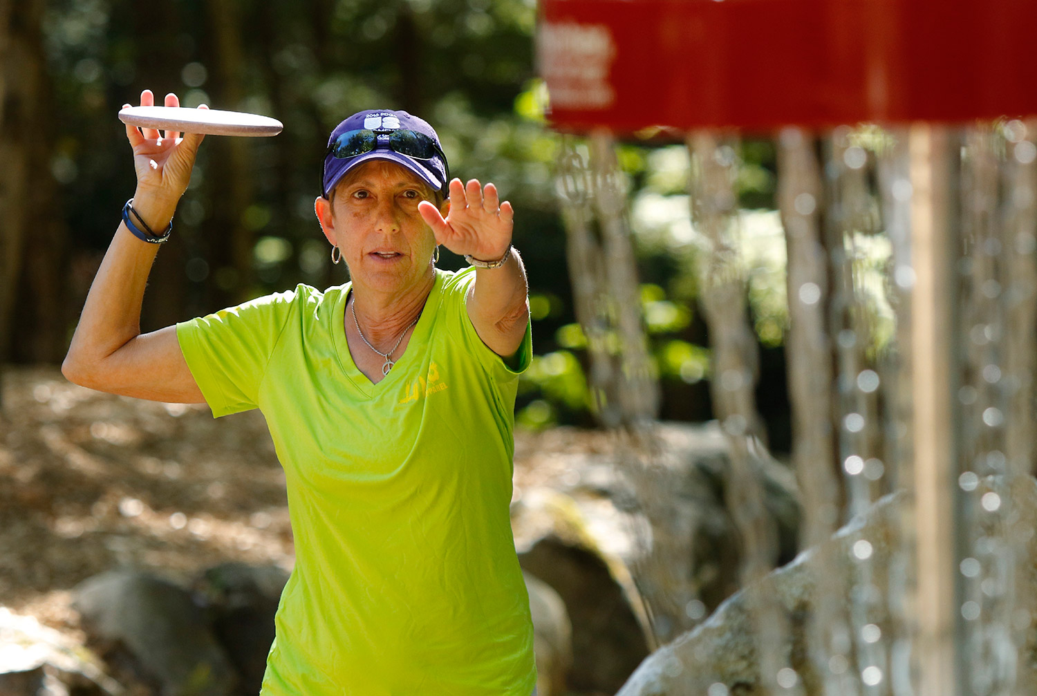 Patti Joseph lines up a throw near a basket while practicing Wednesday at the Sabattus Disc Golf course. Joseph, from Florida, is one of nearly 100 women from 30 states and three countries competing in the U.S. Women's Disc Golf Championship this Friday through Sunday at Sabattus Disc Golf. Gregory Rec/Staff Photographer