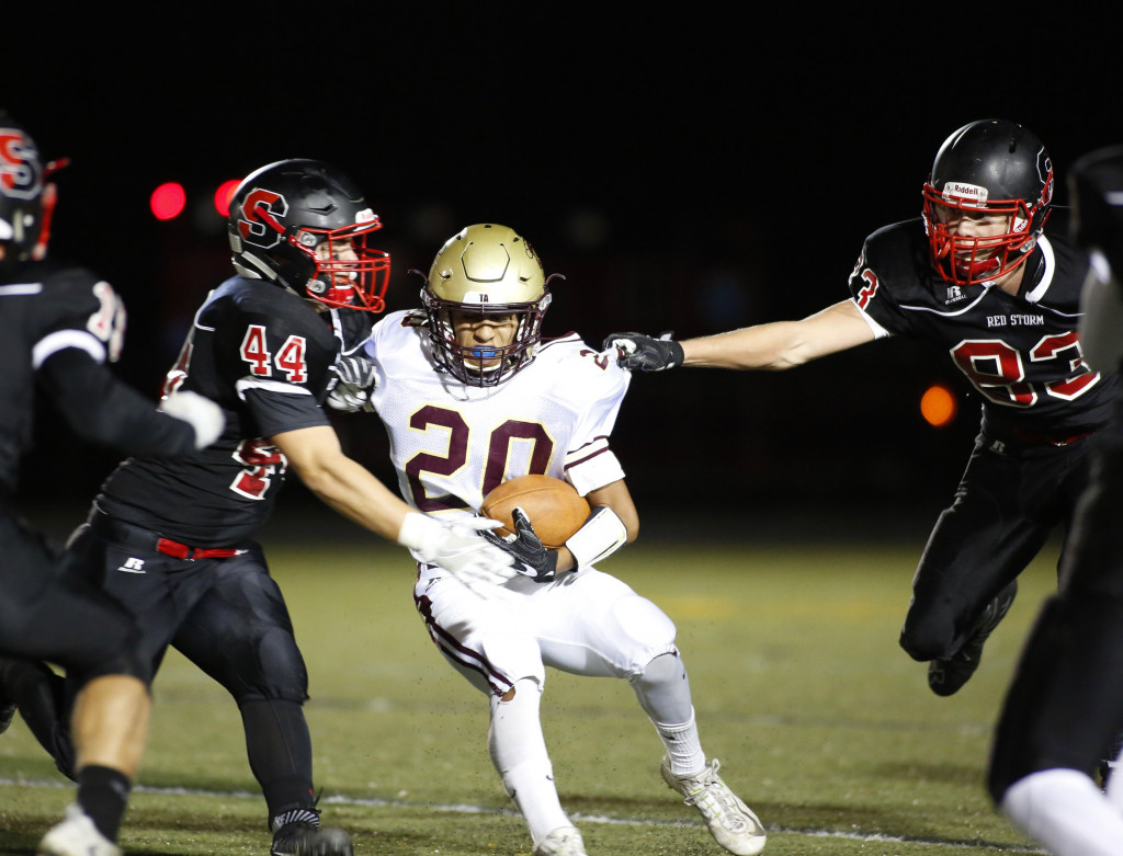 Reece Lagerquist of Scarborough grabs the jersey of Anthony Bracamonte of Thornton Academy as Matthew Cook of Scarborough comes in for the tackle. Derek Davis/Staff Photographer