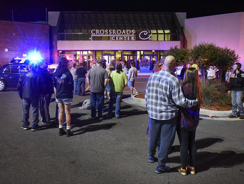 People stand near an entrance of the Crossroads Center mall in St. Cloud, Minn., as officials investigate the multiple stabbings on Saturday evening.